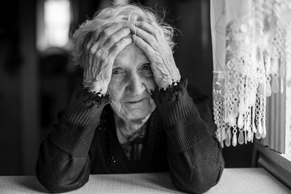 Mustavalkoinen kuvituskuva iäkkäästä naispuolisesta henkilöstö, joka nojaa käsiään vasten, katse kameraan.